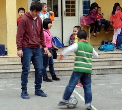 Un volontario segue un alunno di una scuola locale per il progetto di volontariato sportivo in Vietnam
