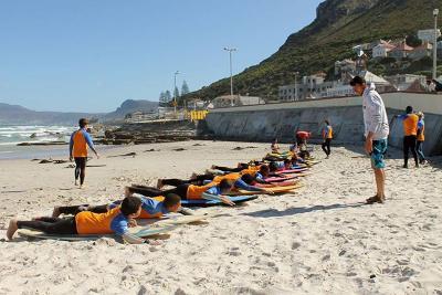 Un volontario con i bambini del progetto di Surf a Cape Town