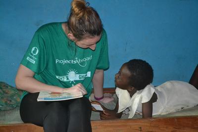 Una volontaria del progetto di servizio sociale in Ghana parla con una bambina ghanese
