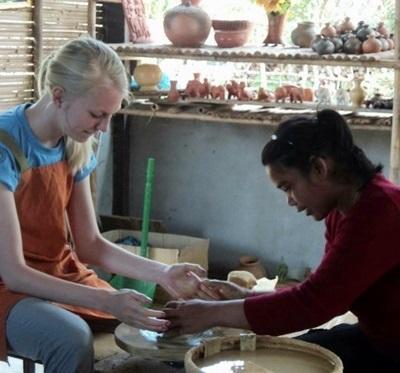Una volontaria del progetto arte e cultura aiuta un'artigiana locale a creare i propri prodotti in Cambogia