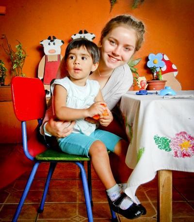 Volontaria del progetto di insegnamento aiuta una bambina in una scuola ad Heredia
