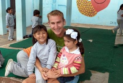 Volontario gioca con bambine durante una missione umanitarie in Ecuador