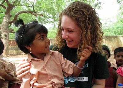 Una volontaria in  missione umanitaria in India accudisce una bambina