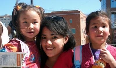 Una volontaria del progetto di insegnamento intrattiene due bambini in Mongolia