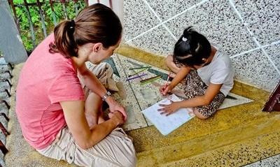 Volontaria insegna ad una bambina a disegnare