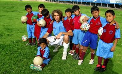 Un volontario del progetto di sport insegna ai bambini a giocare a calcio in Perù