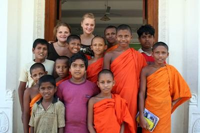 Giovani volontarie del progetto di insegmanento con gli alunni presso un tempio in Sri Lanka