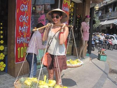 Volontaria trasporta la frutta nel tipico modo vietnamita
