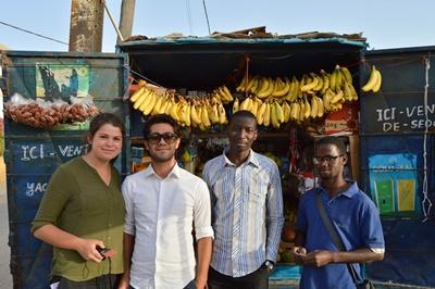 I volontari di Projects Abroad e un ragazzo davanti al negozio che ha aperto grazie al progetto di microcredito in Senegal