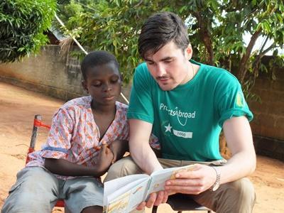 Un volontario di Projects Abroad legge un libro ad un bambino in Togo