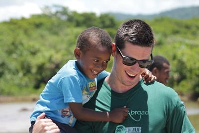 Volontario che gioca con un bambino nel Sud Pacifico.
