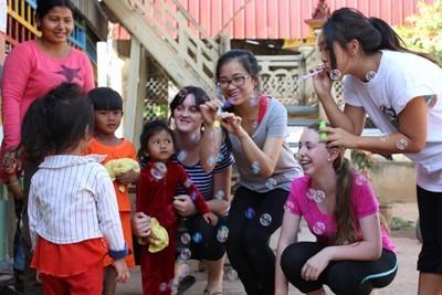 Ragazze volontarie in Cambogia si divertono a giocare con i bambini